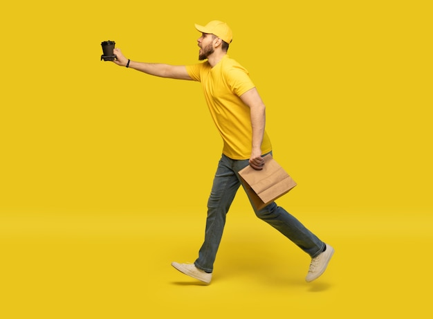 Bezorgservice, fast food en mensen concept - gelukkig man met koffie en wegwerp papieren zak.