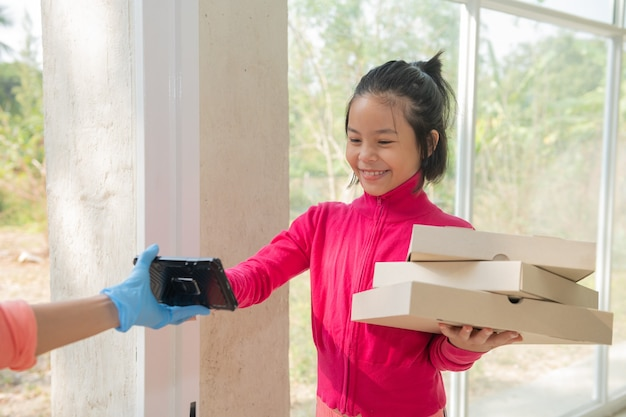 Bezorgservice in t-shirt, in beschermend masker en handschoenen die eten bestellen, pizzadozen voor het huis, jonge vrouw logt in op digitale mobiele telefoon na ontvangst van pakket van koerier. uitbraak van covid-19