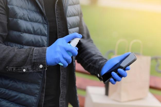 Bezorgservice koerier tijdens het coronavirus, covid-19, pandemie, bijgesneden koerier handen in handschoenen spuiten alcohol desinfecterende spray op mobiel in de buurt van kartonnen dozen buitenshuis