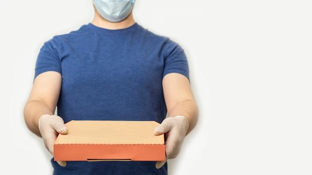 Bezorgservice tijdens quarantaine. bezorger in rubberen handschoenen en beschermend gezichtsmasker houdt doos voor pizza. blijf thuis, online winkelen tijdens de uitbraak van het coronavirus.