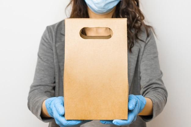 Bezorgservice voor eten tijdens quarantaine vanwege uitbraak van coronavirus. vrouw die een doos in medische handschoenen en beschermend masker houdt.