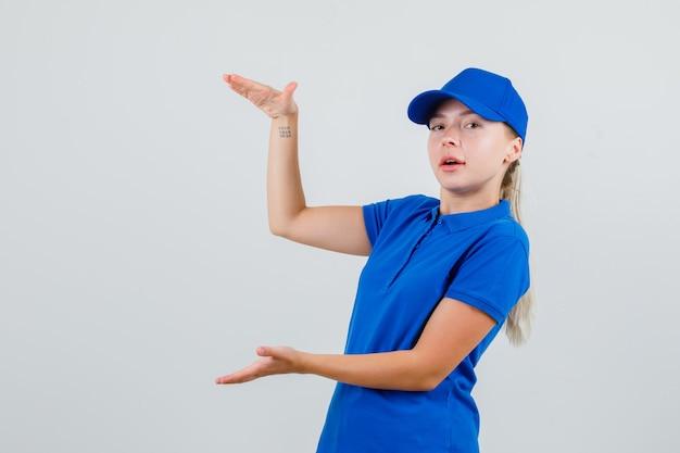 Bezorgvrouw die grootteteken in blauw t-shirt en pet toont en er zelfverzekerd uitziet
