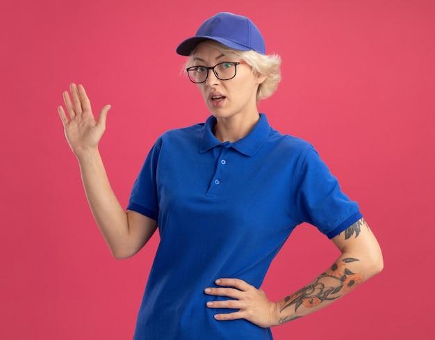 Bezorgvrouw in blauw uniform en pet die verward kijkt en presenteert met arm oh hand over roze muur