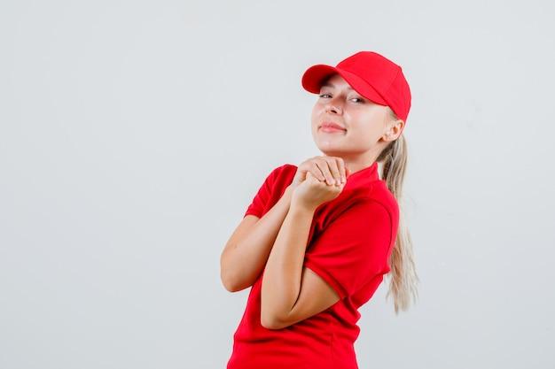 Bezorgvrouw in rood t-shirt en pet die de handen gevouwen houdt en er vrolijk uitziet