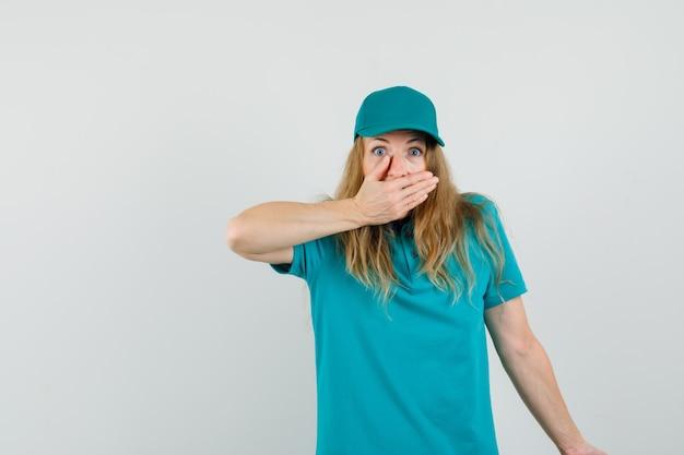 Bezorgvrouw in t-shirt, pet die mond bedekt met hand en bang kijkt