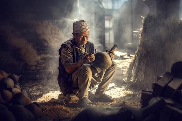 Bhaktapur, nepal -march21 2017: de oude man schildert in een kleipot in durbar-plein in de buurt van oude hindoe-tempels in kathmandu, nepal