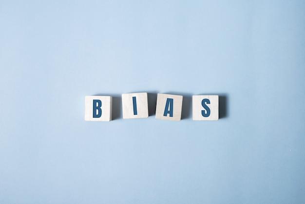 Bias - woord van houten blokken met letters, persoonlijke meningen beoordelen vooringenomenheid concept.