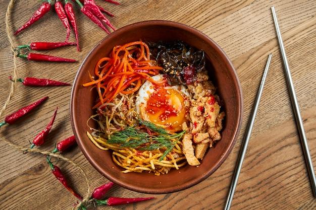 Bibimbap diende als een kom warme witte rijst met daarop namul, kimchi, chilipeperpasta, sojasaus, gebakken ei en gesneden vlees.