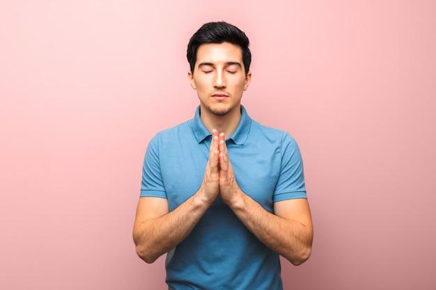 Bid voor amerika. man in blauw shirt bidden voor de wereld opgeslokt door coronavirus pandemie tegen rood roze achtergrond