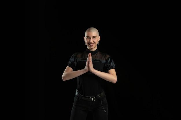 Bidden, lachen. zwart-wit portret van jonge blanke kale vrouw geïsoleerd op zwarte muur. Premium Foto