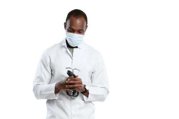 Bidden voor god. mannelijke jonge arts met een stethoscoop en gezichtsmasker op witte studio.