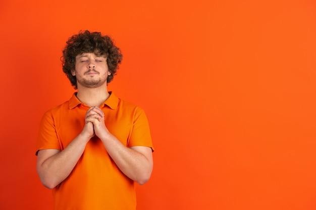 Bidden ziet er kalm uit. zwart-wit portret van de blanke jonge man op oranje muur. mooi mannelijk krullend model in casual stijl. concept van menselijke emoties, gezichtsuitdrukking, verkoop, advertentie.