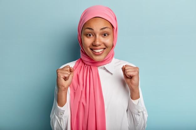 Biddende etnische vrouw heft gebalde vuisten op, verheugt zich over de overwinning, is tevreden met het goede resultaat van het werk, draagt een roze hijab, gekleed in een wit overhemd, geïsoleerd over een blauwe muur. handgebaar. geluk.