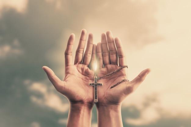 Biddende handen houden een kruisbeeld of kruis van metalen ketting vast met geloof in religie en geloof in god