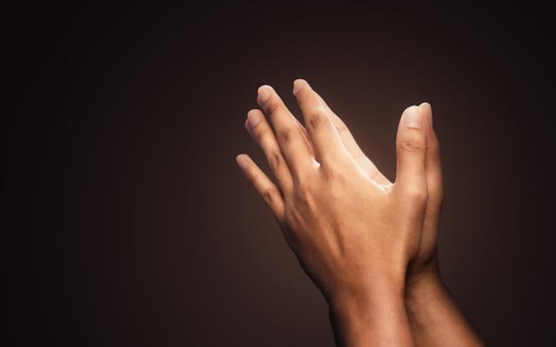 Biddende handen met geloof in religie en geloof in god op donkere achtergrond