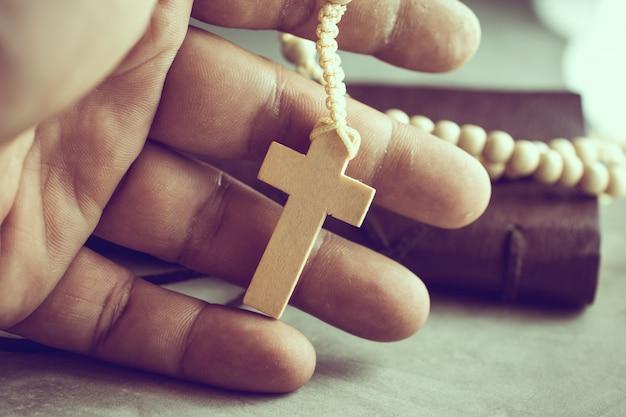 Biddende handen van arme man met een rozenkrans op cement tafel gebed, rozenkrans
