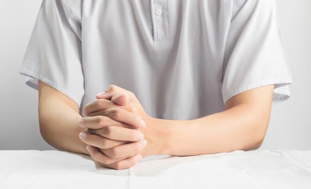 Biddende handen van aziatische mannen dragen witte casual doek geïsoleerd op wit, religie en meditatie