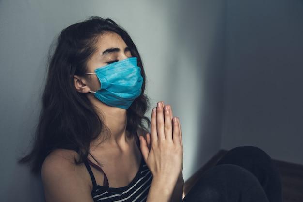 Biddende vrouw gezichtsmasker in de kamer