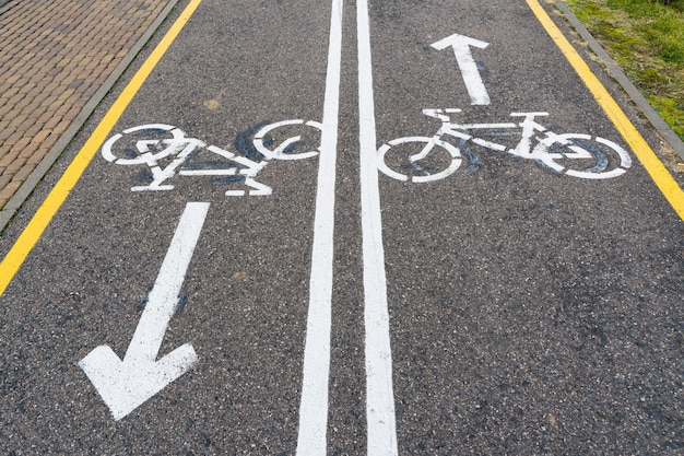 Bidirectioneel fietspad met fietstekens en pijlen die op asfalt worden geschilderd.