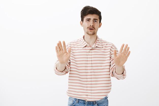 Bied me deze rotzooi niet meer aan. portret van een ontevreden gehoorde volwassen europese man met baard en snor, handpalmen naar zich toe trekken, geen of voldoende gebaar tonen, suggestie afwijzen