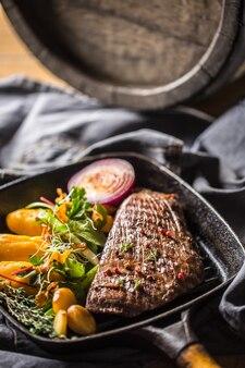 Biefstuk biefstuk in grillpan met batata puree knoflook en kruiden decoratie.