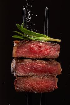 Biefstuk closeup biefstuk snijdt stuk plak medium goed zeldzaam met rozemarijn en vallende zout op een vork met rozemarijn geïsoleerd op zwart