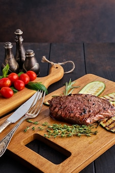 Biefstuk en courgette geserveerd met verse tomatenkers en basilicum op houten snijplank