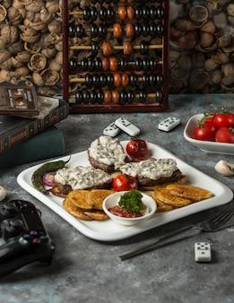 Biefstuk gegarneerd met romige saus, geserveerd met gebakken aubergine, ketcup