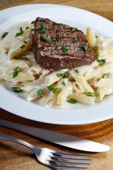Biefstuk geroosterd met penne in witte saus