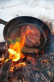 Biefstuk in een koekenpan op een open vuur in een winterbos
