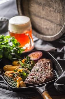 Biefstuk in grillpan met batata puree knoflook kruidendecoratie en tapbier.