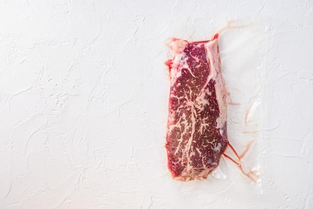 Biefstuk met bovenblad, vacuümverpakt biologisch vlees voor sous vide-koken op witte betonnen gestructureerde achtergrond, bovenaanzicht met ruimte voor tekst.