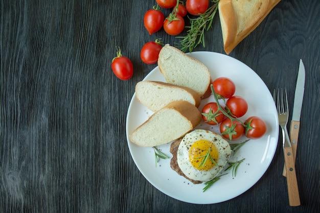 Biefstuk met gebakken ei in kruiden geserveerd op een witte plaat. amerikaans gerecht. donkere houten achtergrond. zijaanzicht. detailopname. ruimte voor tekst.
