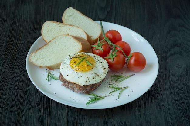 Biefstuk met gebakken ei in kruiden geserveerd op een witte plaat. amerikaans gerecht. donkere houten achtergrond. zijaanzicht. detailopname.