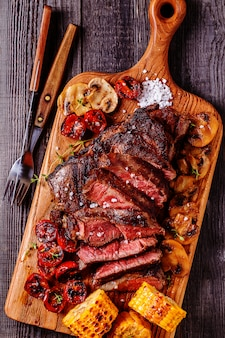 Biefstuk met gegrilde tomaten, champignons en mais.