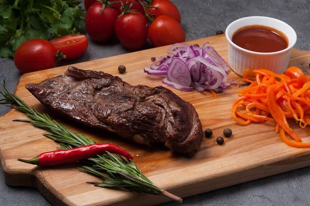 Biefstuk met rode ui, wortel en tomatensaus