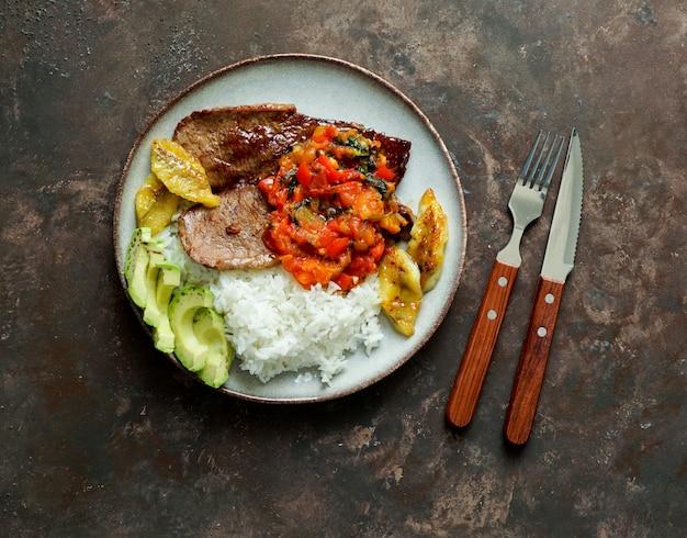 Biefstuk met tomatensaus, rijst, avocado en friet van bananen
