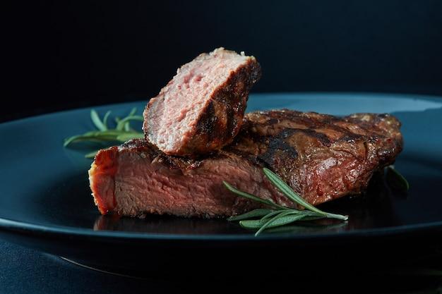 Biefstuk op een zwarte plaat met rozemarijn