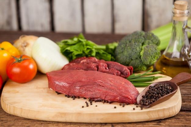 Biefstuk op houten bord met ingrediënten