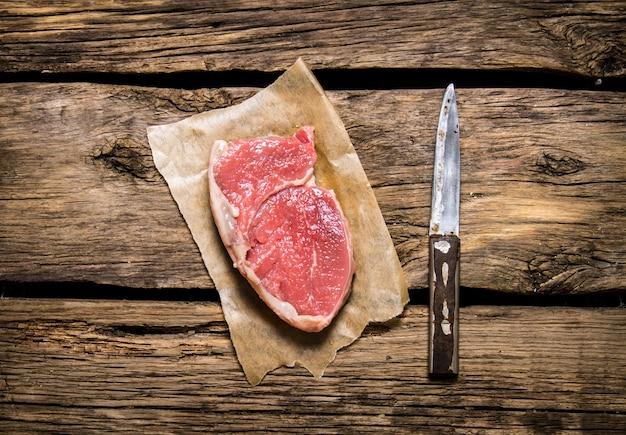 Biefstuk rauw vlees met een mes. op houten achtergrond.