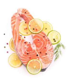 Biefstuk van rode vis en gesneden citroenen op wit