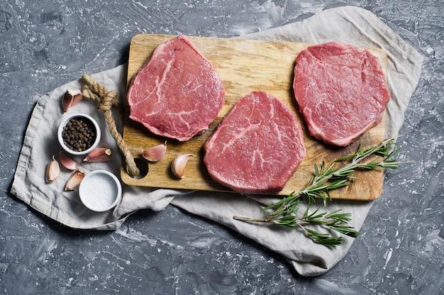 Biefstuk varkenshaasje op een houten snijplank, knoflook en een takje rozemarijn.