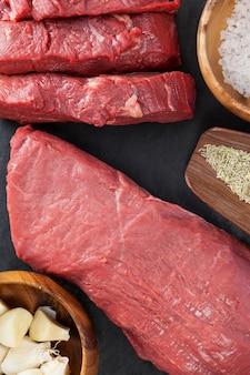 Biefstuk, zout en specerijen op zwarte leisteen plaat