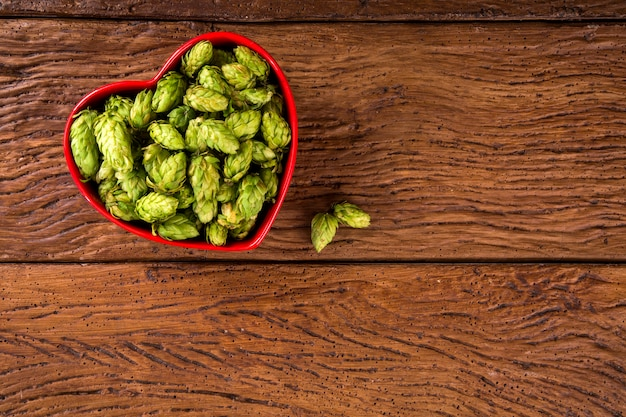 Bier brouwen ingrediënten hopbellen in rood hart kom op houten achtergrond. bierbrouwerij concept.