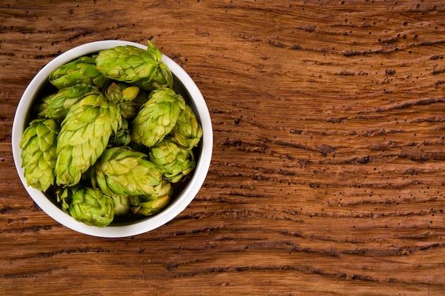 Bier brouwen ingrediënten hopbellen in witte kom op houten achtergrond. bierbrouwerij concept.