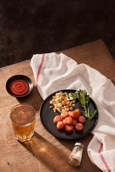 Bier en gegrilde worstjes op houten tafel