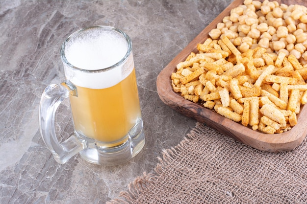 Bier en plaat van crackers en erwten op marmeren oppervlak. hoge kwaliteit foto