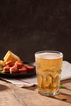 Bier en smakelijke biersnacks set. tabel met mok bier gegrilde worstjes met sauzen.