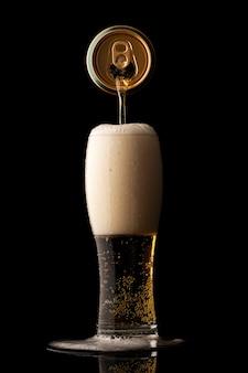 Bier gieten in glas geïsoleerd op zwarte muur