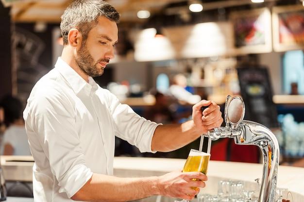 Bier gieten voor klant. zijaanzicht van jonge barman die bier schenkt terwijl hij aan de bar staat